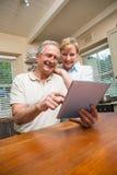 Höga par som tillsammans ser minnestavlaPC Royaltyfria Foton