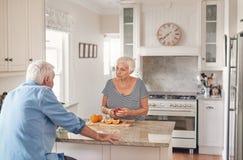Höga par som tillsammans talar, medan förbereda frukosten i deras kök fotografering för bildbyråer