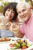 Höga par som tillsammans tycker om mål i utomhus- restaurang Arkivbilder