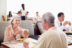 Höga par som tycker om frukosten i hotellrestaurang Fotografering för Bildbyråer