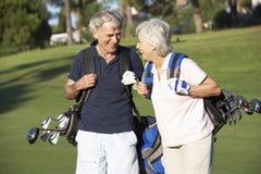 Höga par som tycker om leken av golf Royaltyfria Bilder
