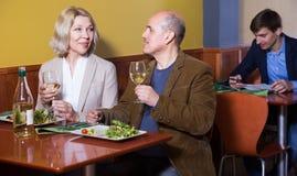 Höga par som tycker om mat i restaurang arkivbilder