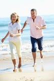 Höga par som tycker om romantisk strandferie Arkivfoto