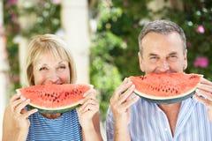 Höga par som tycker om skivor av vattenmelonen Royaltyfria Bilder
