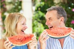 Höga par som tycker om skivor av vattenmelonen Fotografering för Bildbyråer