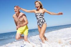 Höga par som tycker om strandferie Arkivfoto
