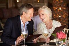 Höga par som väljer från meny i restaurang Arkivbild