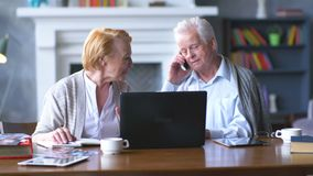 Höga par som websurfing på internet med bärbara datorn Lycklig äldre man och kvinna som använder datoren lager videofilmer
