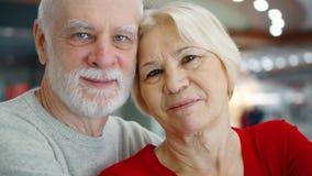 Höga par står i galleriablick på kameran Älska krama pensionärer, i att le för köpcentrum stock video