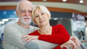 Höga par står i galleriablick på kameran Älska krama pensionärer, i att le för köpcentrum lager videofilmer