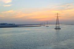 Höga spänningselektricitetskraftledningar som är utdelade till och med havwi royaltyfri foto