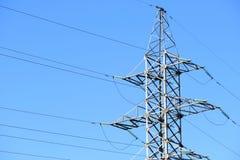 Höga spänningskraftledning- eller tornkraftledningar mot en blå himmel arkivbild