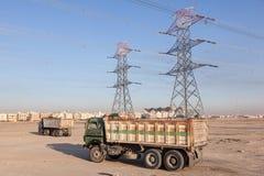 Höga spänningskraftledningar och lastbilar Royaltyfria Foton