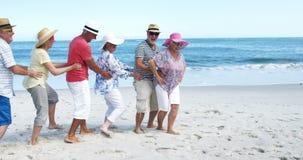 Höga vänner som dansar på stranden arkivfilmer