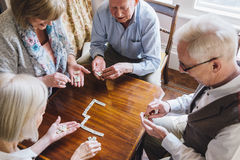 Höga vänner som spelar domino royaltyfria bilder
