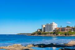 Höga vågor och strandbyggnader på solig dag Royaltyfri Bild