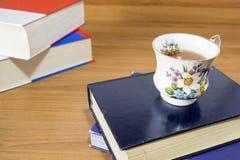 Högar av böcker och en varm kopp te på en wood tabell royaltyfri fotografi