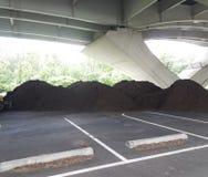 Högar av brun komposttäckning under en bro Arkivbild