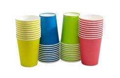 Högar av de disponibla pappers- kopparna i olika färger Arkivfoton