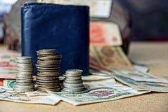 Högar av gamla mynt på pappers- räkningar nära handväskan royaltyfria bilder