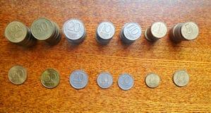 Högar av gamla mynt på tabellen arkivbilder