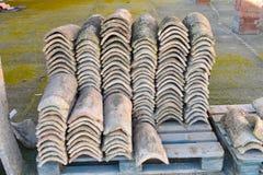 Högar av gamla taktegelplattor i många rader med olikt nummer i någon kolonn De forntida tegelplattorna befläckas med damm och la fotografering för bildbyråer