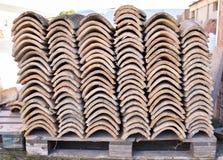 Högar av gamla taktegelplattor i många rader med olikt nummer i någon kolonn De forntida tegelplattorna befläckas med damm och la royaltyfri bild