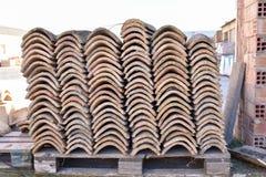 Högar av gamla taktegelplattor i många rader med olikt nummer i någon kolonn De forntida tegelplattorna befläckas med damm och la royaltyfri foto