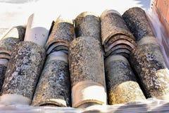 Högar av gamla taktegelplattor i många rader med olikt nummer i någon kolonn De forntida tegelplattorna befläckas med damm och la arkivfoto