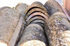 Högar av gamla taktegelplattor i många rader med olikt nummer i någon kolonn De forntida tegelplattorna befläckas med damm och la royaltyfri fotografi