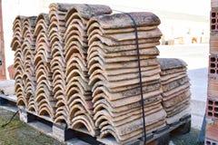 Högar av gamla taktegelplattor i många rader med olikt nummer i någon kolonn De forntida tegelplattorna befläckas med damm och la arkivfoton
