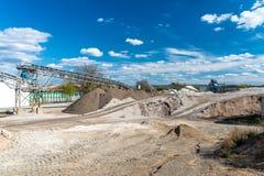 Högar av grus och som krossar på blå himmel på en industriell cementväxt royaltyfri foto