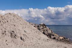 Högar av grus på konstruktionsplatsen på havet under ljus blå himmel royaltyfri fotografi