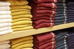 Högar av mångfärgad kläder på hyllorna i lager royaltyfri bild