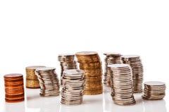högar av mynt på vit bakgrund Arkivbild