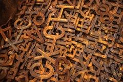 Högar av rostiga metallnummer och bokstäver Arkivfoto