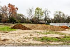 Högar av smuts hauled in i vakant bostads- lott i tidig vår till förberett för konstruktion arkivbild