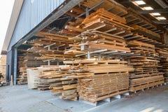 Högar av träplankor i ladugård Arkivbilder