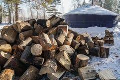 Högar av vedträt på snöig jordning i vintern för spis och värme i kabin royaltyfri bild