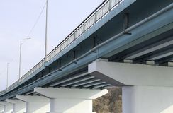 Högar under bron Lång konkret bro över en bred flod på en solig dag Royaltyfri Fotografi