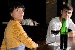 Högdragen ung kvinna som dricker i en bar royaltyfri foto