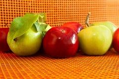 Högen av äpplen på den orange bakgrunden Arkivbilder