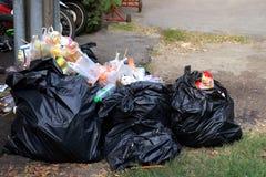 Högen av avskrädeplast-svart och avfallpåsen slöser bort många på golvet, föroreningavfallet, plast-avfallsen och avskrädet för p royaltyfria foton