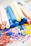 Högen av den krossade den kritacloseupen och regnbågen färgade pastellfärgade färgpennor Arkivbild
