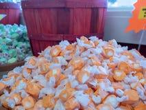 Högen av den orange anstrykningsmickergodisen på försäljning i godis shoppar royaltyfri fotografi