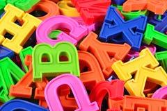 Högen av det plast- färgade alfabetet märker tätt upp Arkivfoto