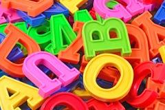 Högen av det plast- färgade alfabetet märker tätt upp Arkivbild
