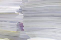 Högen av dokument på skrivbordet staplar upp högt att vänta som ska klaras av Royaltyfri Foto