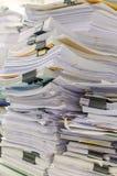 Högen av dokument på skrivbordet staplar upp högt att vänta som ska klaras av Arkivfoton