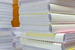 Högen av dokument på skrivbordet staplar upp högt att vänta som ska klaras av Arkivbilder